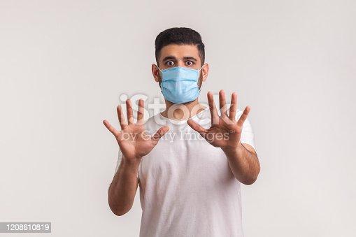 istock Alarming scared panicking man in hygienic mask gesturing stop, afraid of coronavirus infection 1208610819