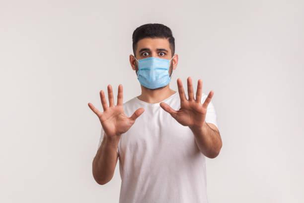 Alarming scared panicking man in hygienic mask gesturing stop, afraid of coronavirus infection stock photo