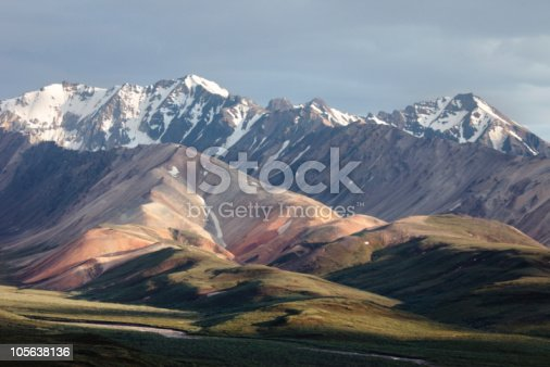 Late evening sun pouring over the foothill and snow covered ridges of Alaska Range in Denali National Park