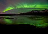The Aurora shine bright over an Alaskan mountain range.