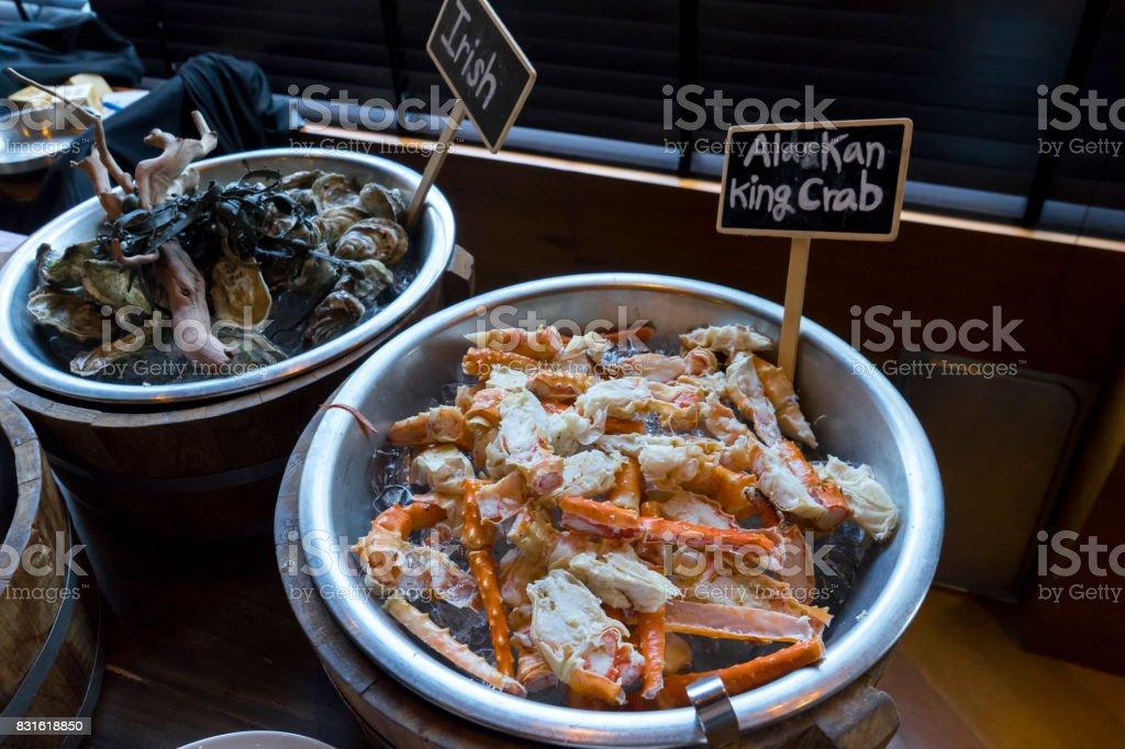 alaskan king crab oysters irish tiger prawn and lemon on ice stock photo