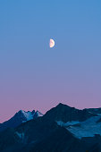 Alaskan mountains with half moon and pink skies after sunset during blue hour