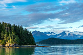 Distant snowcapped mountains in Juneau, Alaska with forest area headland in foreground.