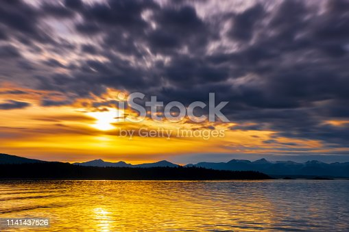 Alaskan sunset over the sea with distant mountains.