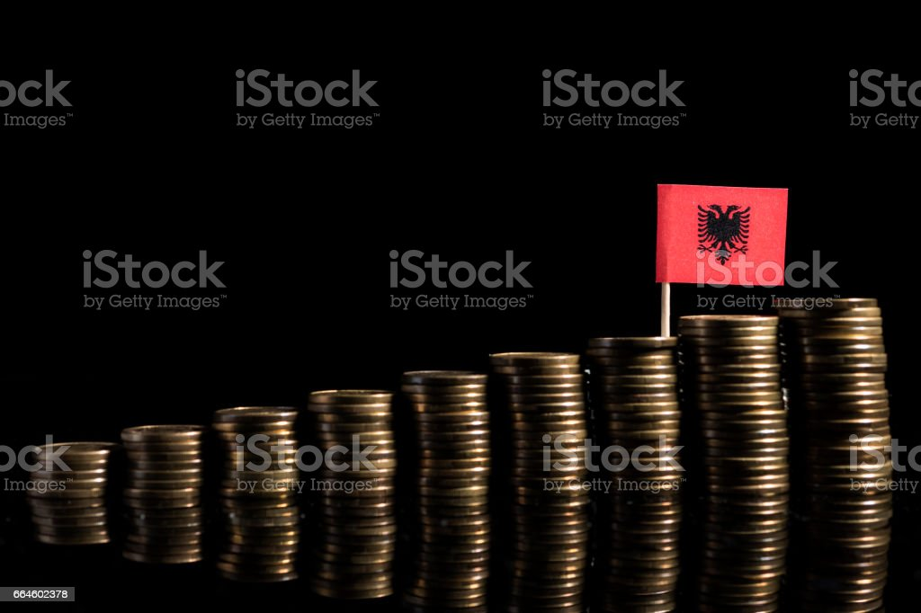 Albanian flag with lot of coins isolated on black background stock photo