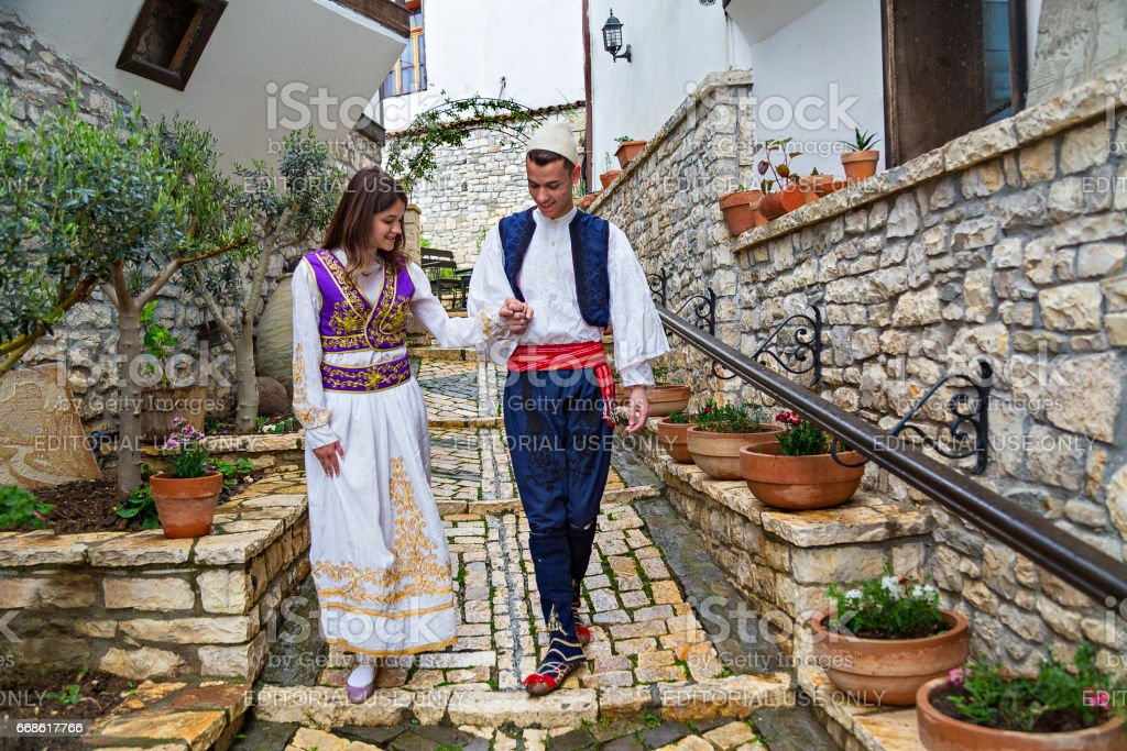 Albanian man and woman in national costumes walking in the cobble stone street, in Berat, Albania. stock photo