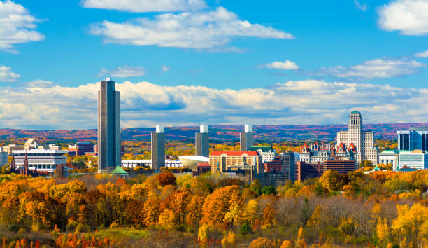 Albany Skyline with Autumn Colored Trees Albany skyline with autumn colored trees in the foreground and rolling, puffy clouds with a blue sky in the background. albany county new york state stock pictures, royalty-free photos & images