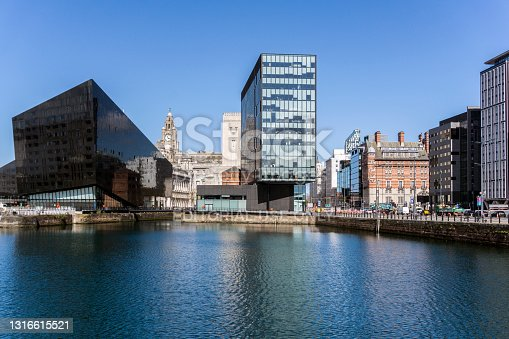 View across the Albert Dock in the center of Liverpool, UK.  Modern buildings can be seen and people can be seen on the promenade.