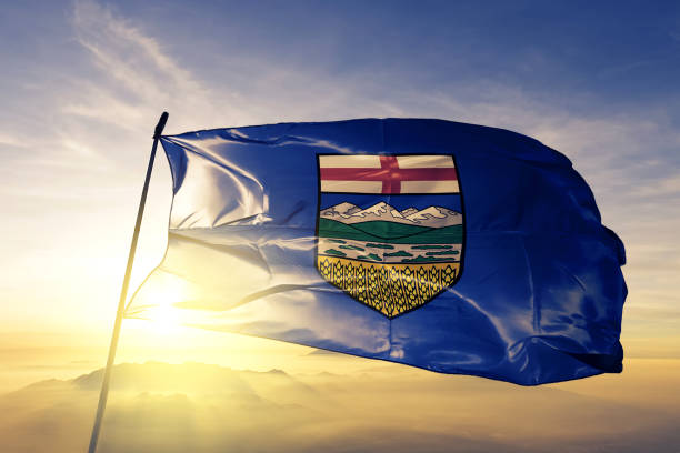 Alberta province of Canada flag textile cloth fabric waving on the top sunrise mist fog stock photo