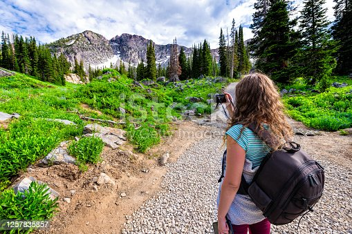 Albion Basin, Utah pine trees with woman taking pictures on summer Cecret Lake trail in 2019 in Wasatch mountains with rocky snow Devil's Castle mountain