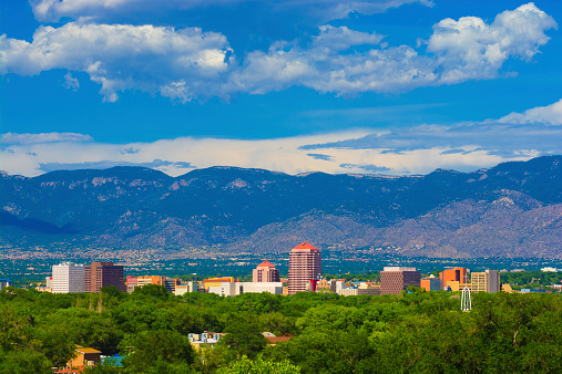 Albuquerque downtown skyline with the Sandia Mountains and clouds in the background.