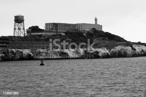 A black and white picture of Alcatraz Island and San Francisco Bay with seagulls flying in the background.