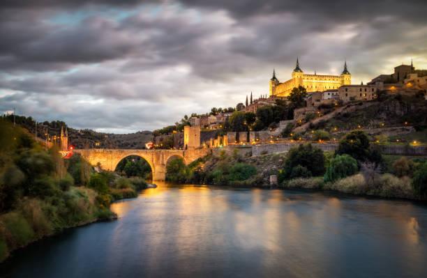 alcazar and alcantara bridge in Toledo at sunset reflected in Tajo river stock photo