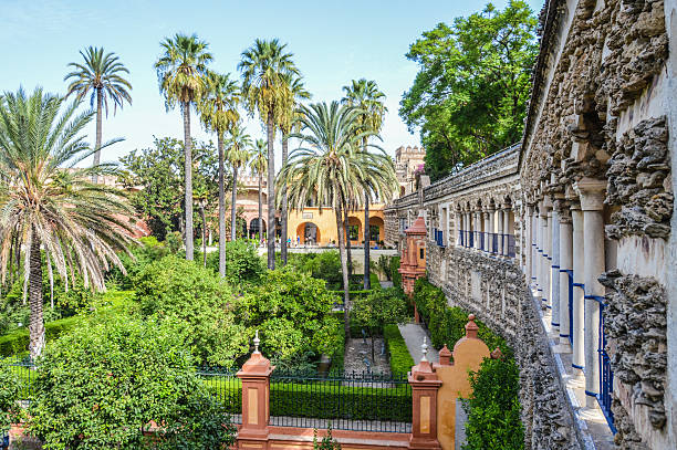 Alcazar gardens in Seville, Spain Seville, Spain - August 11, 2015: The gardens of the Alcazar palace in Seville, Spain. Photo taken during the day and features several tourists enjoying the atmopshere of the gardens. alcazar palace stock pictures, royalty-free photos & images