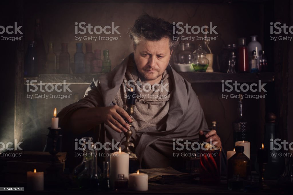 alchemist at the table stock photo