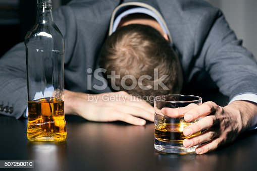 istock alcohol addiction - drunk businessman holding a glass of whiskey 507250010