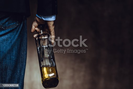 Man holding bottle of whiskey. Alcohol addiction concept.