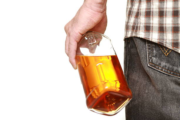 Alcohol addiction drunk man with a whisky bottle head in the sand stock pictures, royalty-free photos & images