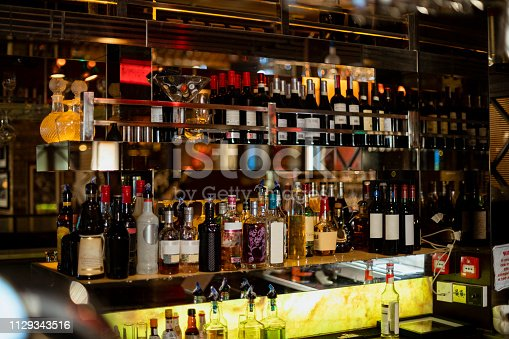 Front view of behind the bar counter in a restaurant. There are bottles of wine and various spirits on shelves.