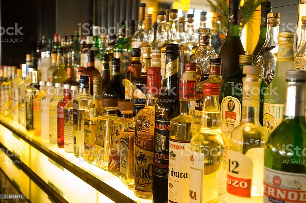 Alcohol bottles on a bar stock photo