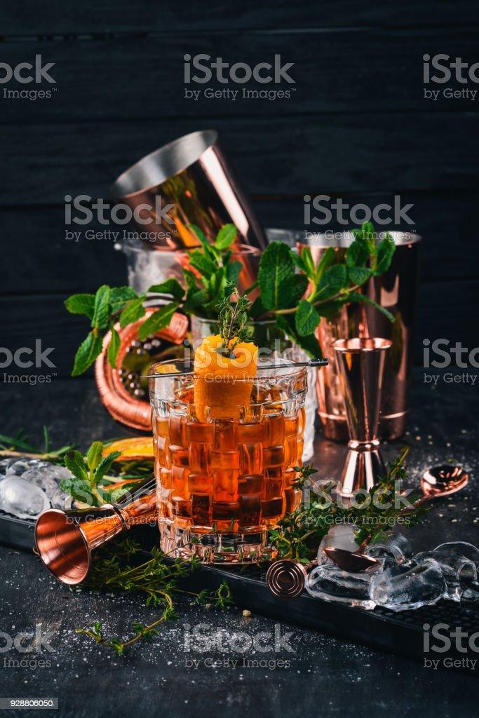 Alcohol Cocktail Negroni. Orange, liquor, ice. On a black wooden background. stock photo