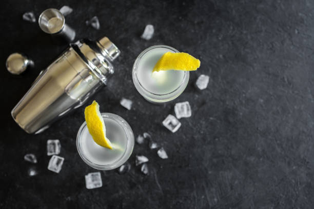 Alcohol Cocktail with lemon and ice Alcohol Cocktail with lemon and ice. Gin tonic fizz or gimlet cocktail on black background, copy space. cocktail shaker stock pictures, royalty-free photos & images