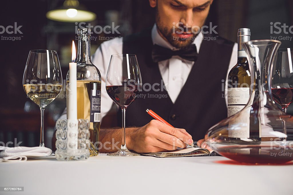 Alcohol critic writing his recommendation stock photo