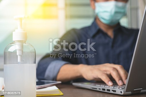 Alcohol gel with male employee wearing a health mask Preventing corona virus infection covid-19 in back, concept of working from home and social distancing.