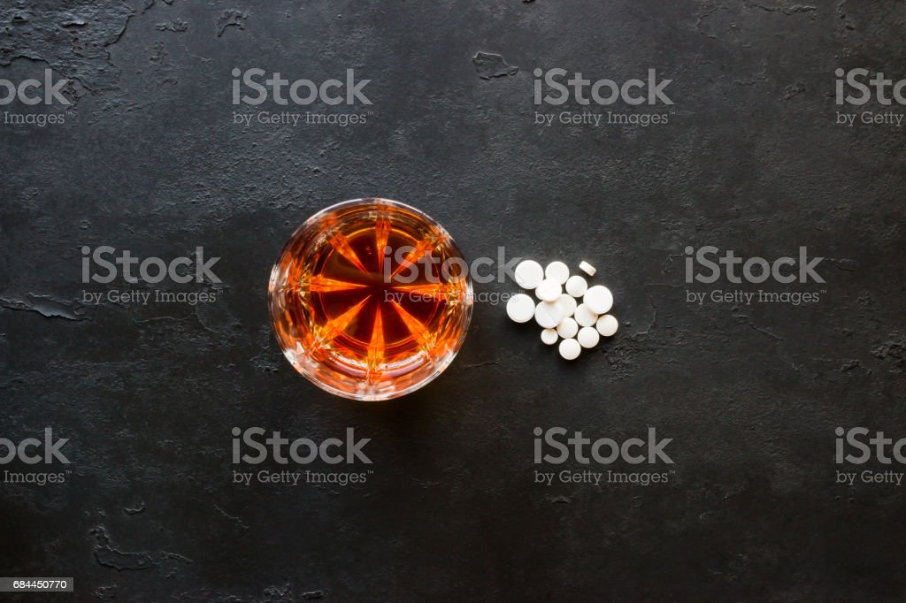 Alcohol in a glass and a handful of pills on a black background stock photo