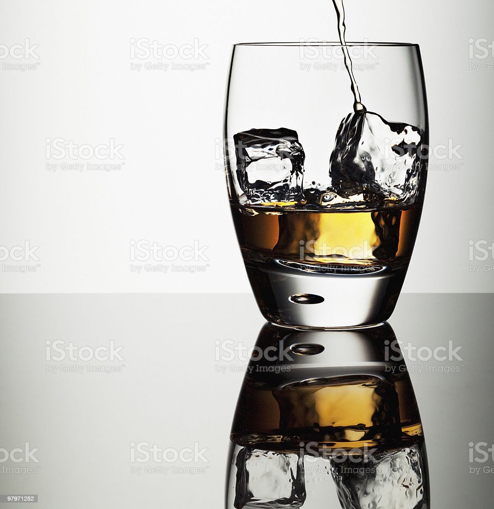 Alcohol pouring into highball glass with ice cubes royalty-free stock photo