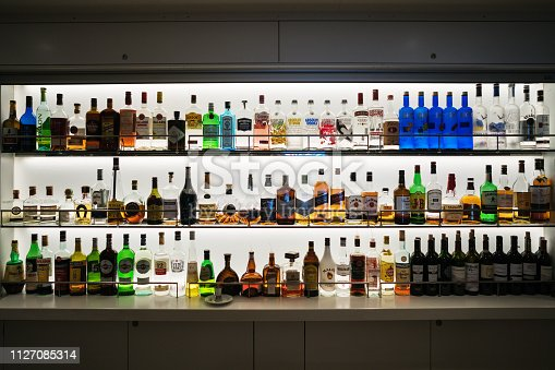 A shelf full of different colored and strenght spirits and drinks in a bar on a cruise ship
