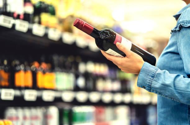 Alkoholregal im Spirituosenladen oder Supermarkt. Frau kauft eine Flasche Rotwein und schaut sich alkoholische Getränke im Laden an. Glückliche weibliche Kunden wählen Merlot oder sangiovese. – Foto