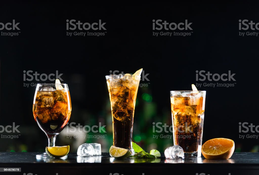 Alcoholic beverages whiskey and cola in glasses of different shapes on the bar table. royalty-free stock photo