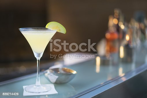 istock Alcoholic cocktail apple martini shot at bar with counter bar in background. 839214426