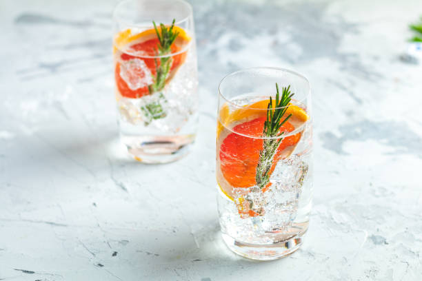 Alcoholic cocktail with grapefruit, soda, ice, gin and rosemary stock photo