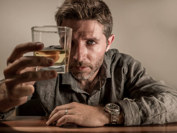 alcoholic depressed and wasted addict man sitting in front of whiskey glass trying holding on drinking in dramatic expression suffering alcoholism and alcohol addiction isolated on grey background - dipsomania stock pictures, royalty-free photos & images