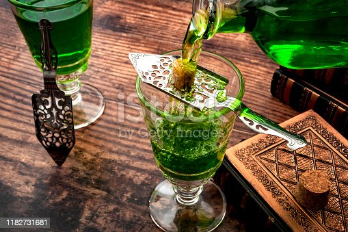 Alcoholic drink, creative stimulant and bohemian lifestyle concept theme with a vintage glass bottle pouring absinthe over a sugar cube in a stainless steel spoon next to books on a wooden table