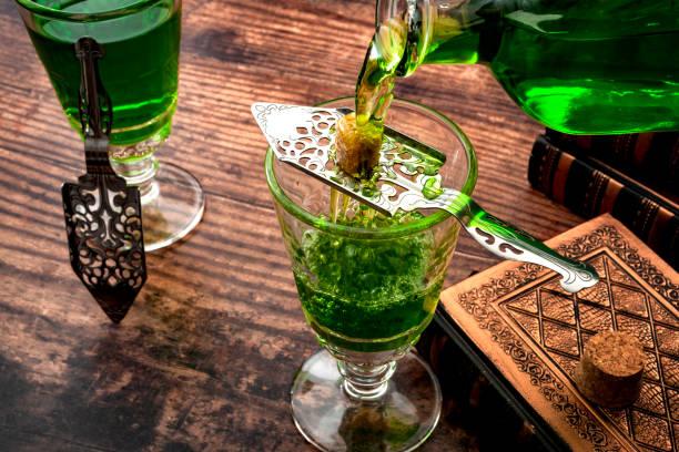 Bebida alcohólica, estimulante creativo y tema de concepto de estilo de vida bohemio con una botella de vidrio vintage vertiendo absenta sobre un cubo de azúcar en una cuchara de acero inoxidable junto a libros en una mesa de madera - foto de stock