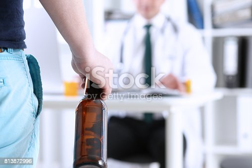 istock Alcoholic hold in hand empty bottle at doctor reception 813872996