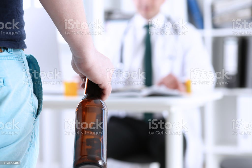 Alcoholic hold in hand empty bottle at doctor reception stock photo