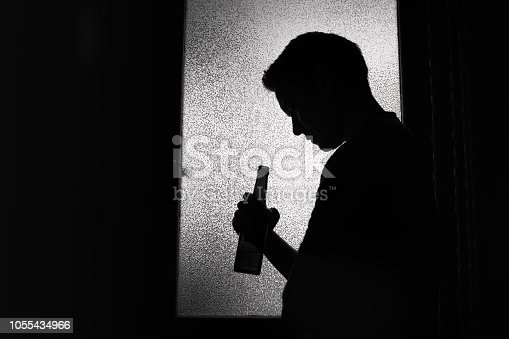Unrecognizable sad man drinking a beer alone in a dark room.