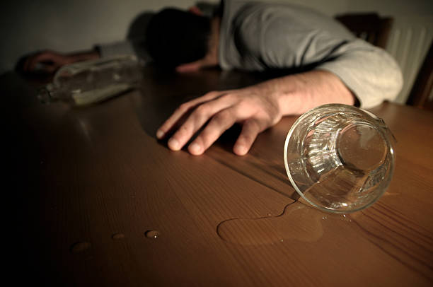 Alcoholism Concept Man Drunk Laying on the Table stock photo