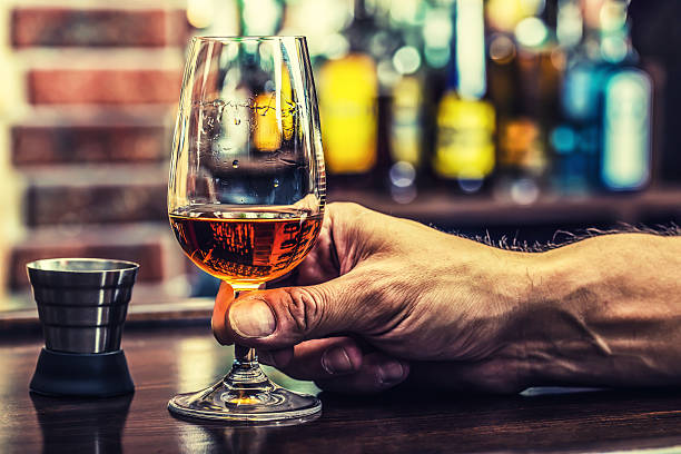 Alcoholism. Hand alcoholic and drink the distillate brandy or cognac. stock photo