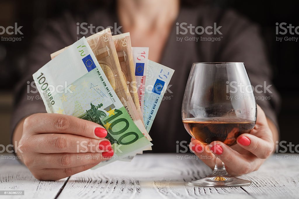 Alcoholism issue. Female take wine glass on dark toned table stock photo