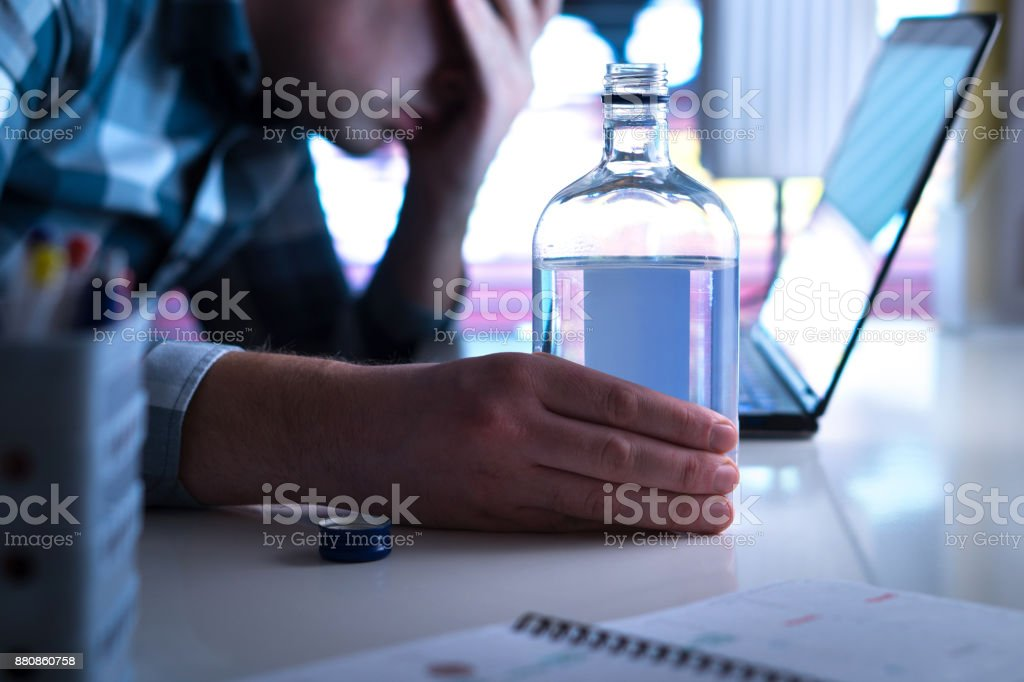 Alcoholism or drinking problem concept. Alcoholic with vodka bottle on table. stock photo