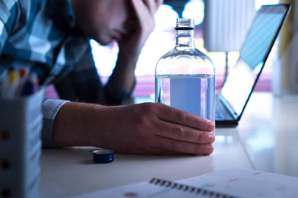 Alcoholism or drinking problem concept. Alcoholic with vodka bottle on table. Alcoholism or drinking problem concept. Alcoholic with vodka bottle on table. Man and alcohol late at night. Drunk at work or in home office. drunk stock pictures, royalty-free photos & images