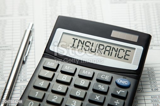 istock alculator with the inscription on the INSURANCE display on the paper tables. Concept medical insurance, car, home or touristic insurance 1047554248