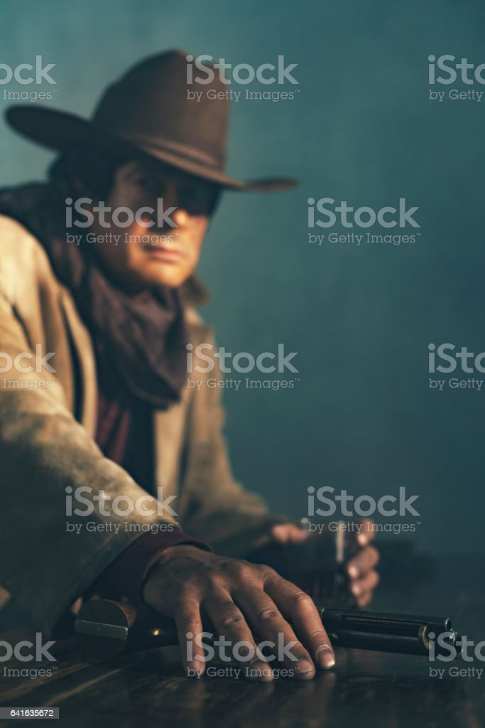 Alert retro late 1960s mexican western actor sitting at bar holding revolver. stock photo