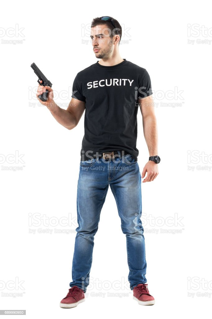 Alerted cautious plain clothes policeman holding gun looking away. stock photo