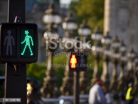 Paris, France - 05/17/2016 : Green signal and red signal at the traffic light for pedestrian crossing, against the background of street lamps of the Alexandre III bridge spanning the Seine.